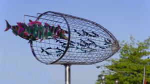 """Kinetische Objekt """"Fisch-Netz-Jäger - gefährdete Fische und Menschen"""" des Künstlers Rainer Wiedemann steht auf dem Fährplatz vor der alten Vogtei ©TraveMedia"""